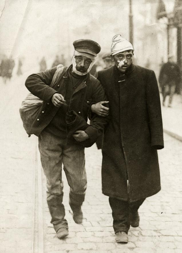 Een Duitse en Belgische gewonde ondersteunen elkaar. (Bron: https://commons.wikimedia.org/wiki/File:Eerste_Wereldoorlog,_gewonden_(3019096514).jpg?uselang=nl)